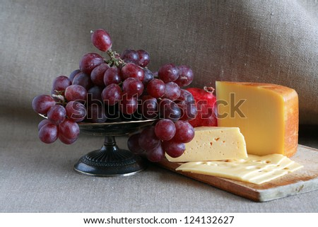 Still life with few sorts of cheese on wooden hardboard near fruits