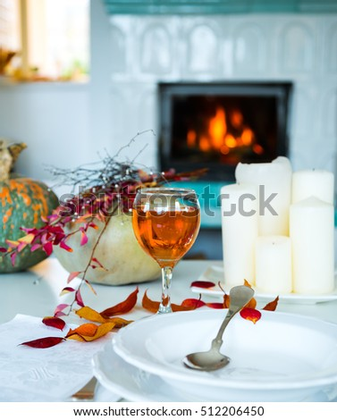 Still life with fire,pumpkin,colorful leaves,candles and punch