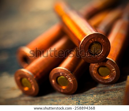 Still life with five rifle cartridges on vintage wooden surface. instagram image retro style