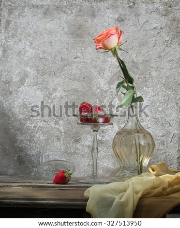 still life with flower and strawberries in a glass vase - stock photo
