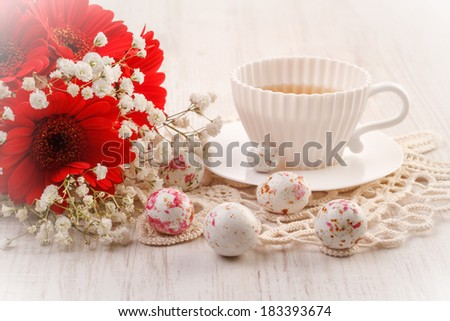 Still life with flowers, cup of tea and easter chocolate candy  - stock photo