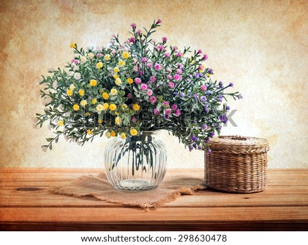 Still life with flowers on wooden table over grunge background - stock photo