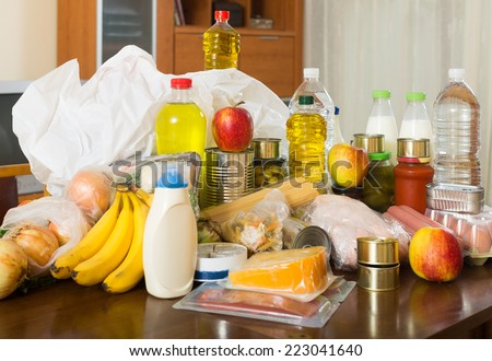Still life with food purchases on table in home - stock photo