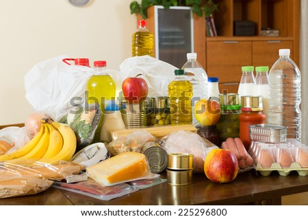 Still life with foodstuffs of supermarket on table in home interior - stock photo