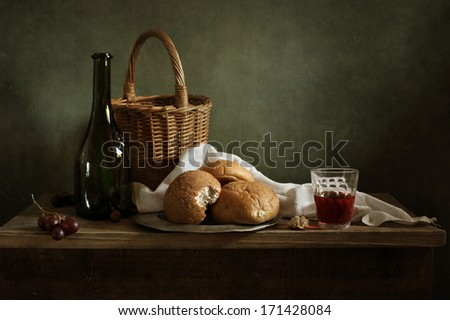 Still life with fresh bread and a glass of red wine - stock photo