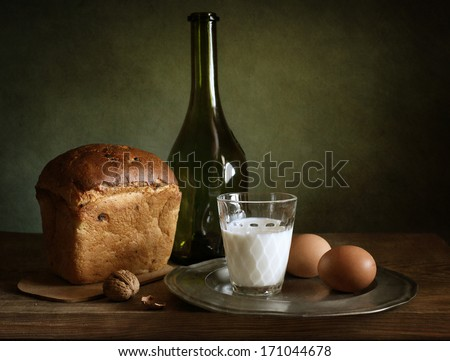 Still life with fresh bread, eggs and a glass of milk - stock photo