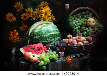 Still-life with fresh fruit red wine and a bright magnificent bouquet, red wine in a transparent wine-glass and a juicy ripe sweet water-melon and fragrant apples with clusters of green juicy grapes  - stock photo