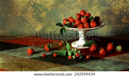 Still life with fresh ripe red berries and ceramic pedestal plate for fruit on abstract mottled background - stock photo