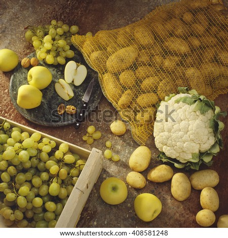 Still life with fresh white grapes in a wooden crate, potatoes in a string bag, cauliflower and apples on a cutting board - stock photo