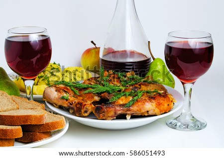 Still-life with fried chicken, red wine, potatoes and bread.