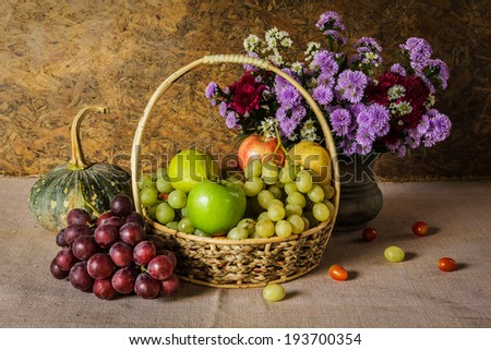 Still Life with Fruit baskets are arranged with a beautiful vase of flowers. - stock photo