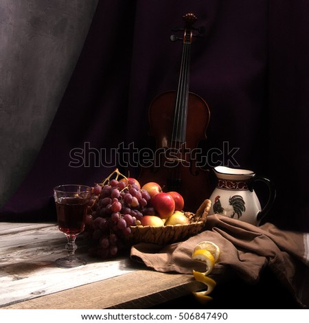 Still life with fruit in wicker basket with violin.