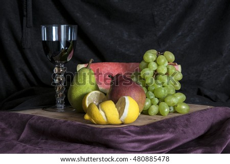 Still life with fruits on wood on black and violet fabric  background