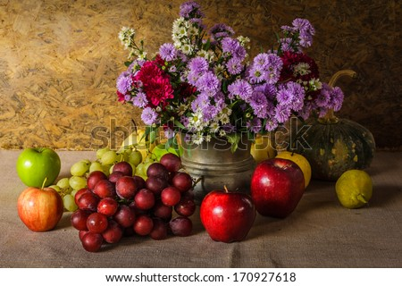 Still life with Fruits were placed together with a vase of flowers beautifully. - stock photo