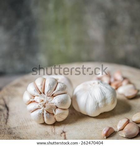 Still-life with garlic on wood cutting board - stock photo