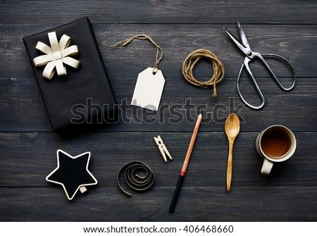 still life with gift box wrapped in black paper and the contents of a workspace composed. Different objects on wooden table.Flat lay.Christmas (xmas) or New year gift packing. Holiday decor concept. - stock photo