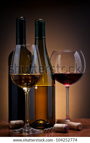 still life with glass and bottles of red and white wine - stock photo