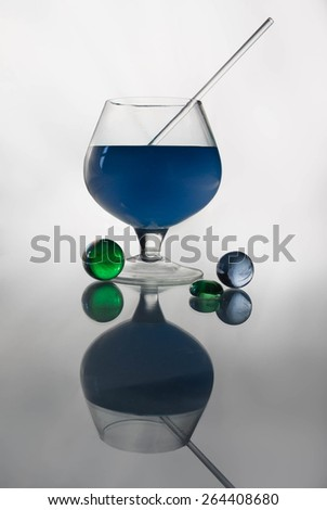 still life with glass balls and goblet with blue curacao - stock photo