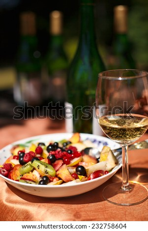 Still life with glass of white wine and fruits