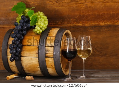 Still life with glasses of red and white wine, barrel with grapes - stock photo
