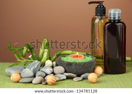 Still life with green bamboo plant and stones, on bamboo mat on color background