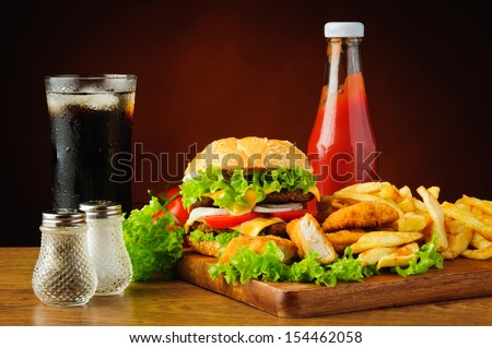 still life with hamburger, chicken nuggets, french fries, cola drink and tomato ketchup - stock photo
