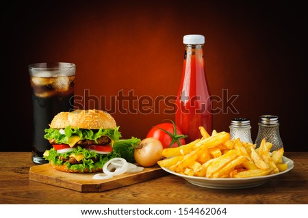 still life with hamburger menu, french fries, cola drink, tomato ketchup, salt and pepper - stock photo