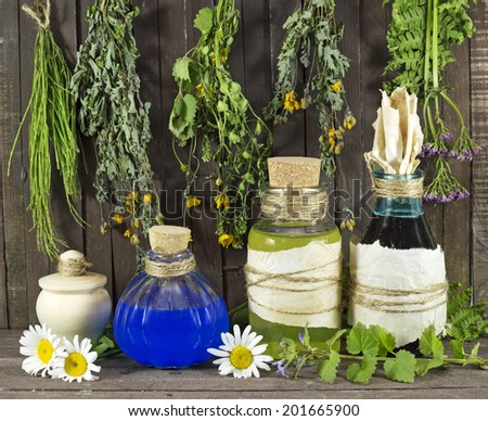 Still life with healing herbs and medical bottles on wooden shelf - stock photo