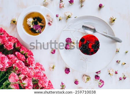 Still life with herbal tea, cake and roses on wooden background. Shabby-chic - stock photo
