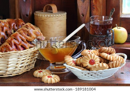 Still-life with honey both an appetizing pie and fresh tea, fragrant honey in a transparent vase and an unusual rake for honey and a sweet pie with a berry stuffing and sugar cookies with jam and tea - stock photo