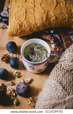 Still life with hot steaming green tea standing on a wooden table near several knitted sweaters, figs and nuts - stock photo