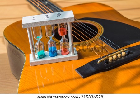 still life with hourglass on guitar on wooden table. - stock photo