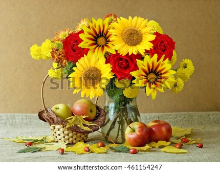 Still life with huge bunch of autumn flowers, sunflowers and red roses, apples and  berries