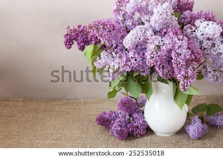 Still life with huge lilac flowers bunch in vase on artistic background - stock photo
