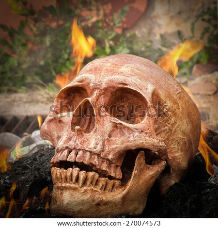 Still life with human skull on fire