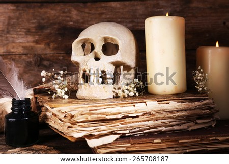 Still life with human skull, retro book and quill on wooden table, closeup