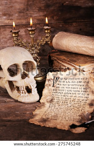 Still life with human skull, retro letter and candlelight on wooden table, closeup