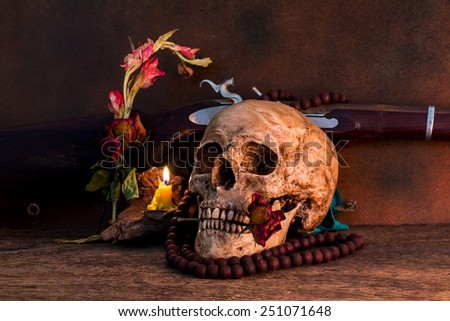 Still life with human skull with dry rose in the mouth, old gun
