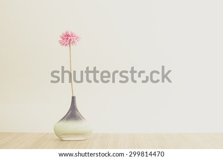 still life with jug and pink flower on the top of wooden table - stock photo