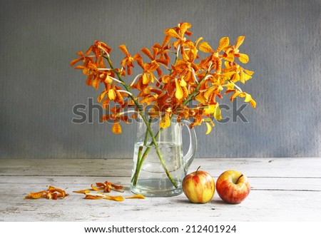 still life with jug of orchid and apple on wooden table. - stock photo