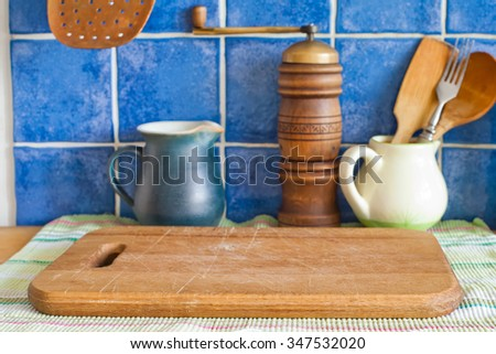 Still life with kitchen accessories. Green jug, hand grinder, vintage wooden spoons, cutting board on napkin. Blue tile ceramic background.  - stock photo