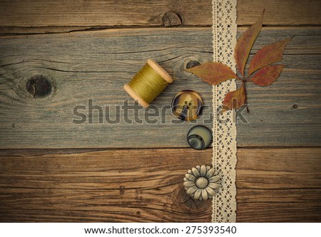 still life with lace ribbon, vintage buttons, spools of thread and dry  on the surface of an old wooden table. instagram image retro style