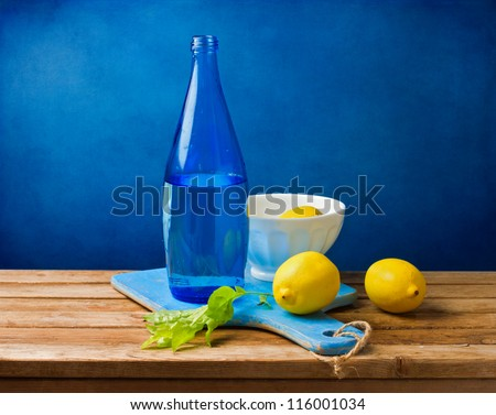 Still life with lemons and blue bottle on wooden table over grunge blue wall - stock photo