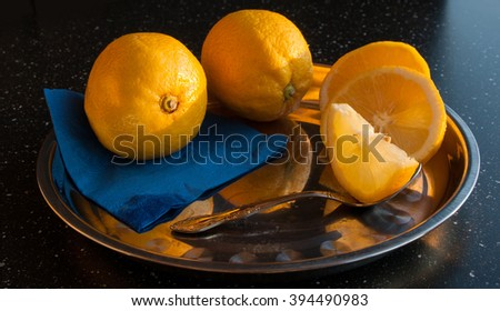 Still life with lemons on a silver tray on a dark background