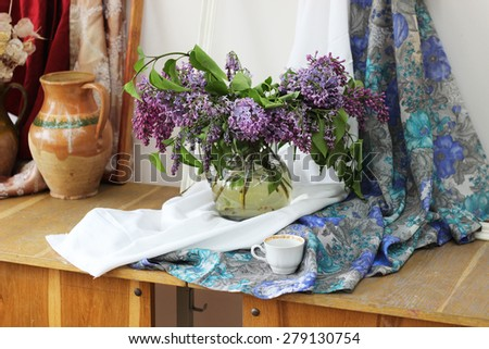 still life with lilac in glass vase and white cup - stock photo