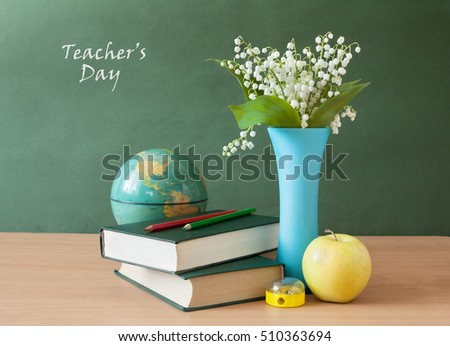 Still life with lily of valley bunch, books pile, apple and pencils on blackboard. Teacher's day concept
