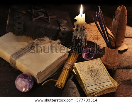 Still life with magic objects, books, candles and the tarot cards.  Halloween and magic still life, fortune telling seance or black magic ritual with mysterious occult and esoteric symbols  - stock photo