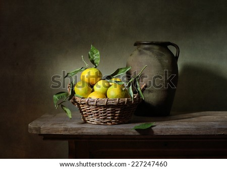 Still life with mandarins and an old jar - stock photo