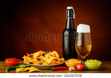 still life with nacho tortilla chips, cheese, salsa guacamole dip and beer
