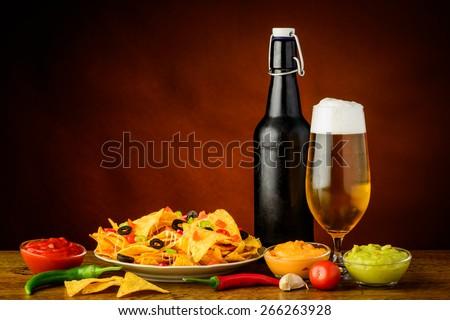 still life with nacho tortilla chips, cheese, salsa guacamole dip and beer - stock photo